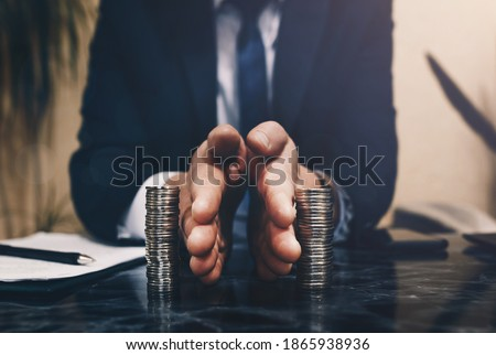 Businessman separates stack coins. Concept of  saving and investing.  Property division. Divorce and legal services. Foto d'archivio ©