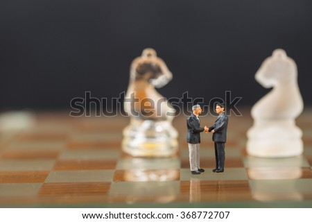 Businessman shake hands for good corporate business with chess game concept. #368772707