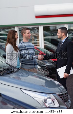 Businessman shaking hand  of a man in a dealership