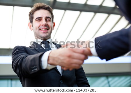 Businessman shaking hands at the office on blurred background