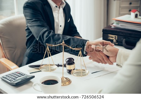 Businessman shaking hands to seal a deal with his partner lawyers or attorneys discussing a contract agreement #726506524