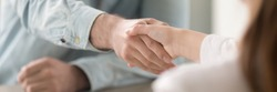 Businessman shaking hands with businesswoman, client and agent greeting gesture. Two people handshaking expressing respect and trust concept. Horizontal close up photo banner for website header design