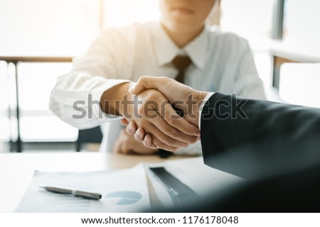 Businessman shaking hands with customer in office. #1176178048