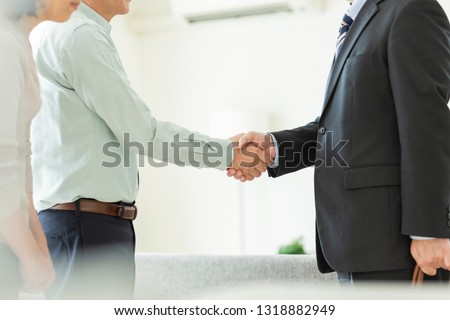 Businessman shaking hands with middle-aged couple