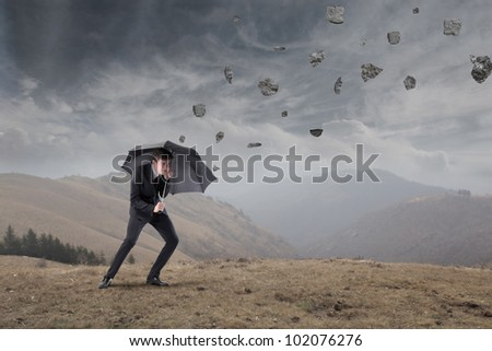 Businessman sheltering under an umbrella from rocks falling to the ground