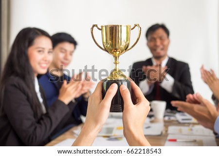 Businessman show thumbs up with trophy, reward, winner, champion and successful for business #662218543
