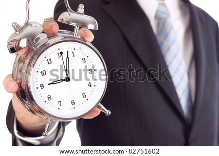 Businessman showing an alarm clock, aiming four past nine.