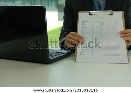 businessman showing auto insurance quote request form #1315818116