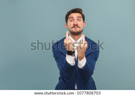 Businessman showing fuck sign at camera. Business people concept, richly and success. Indoor, studio shot on light blue background