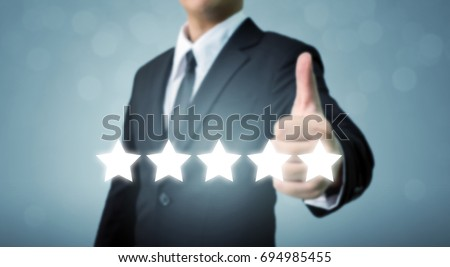 Businessman showing hand sign thumb up and five star symbol to increase rating of company, The excellence of the business or service concept