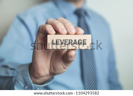 Businessman showing Leverage word in wooden block.