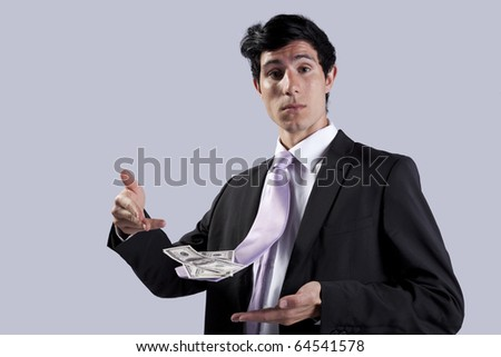 Businessman showing money in his flying necktie (isolated on gray) - stock photo
