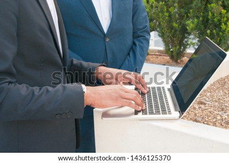 Businessman showing presentation on computer to his colleague. Hands of man in office suit using laptop. Using laptop concept