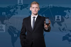 Businessman showing smartphone and world map in background
