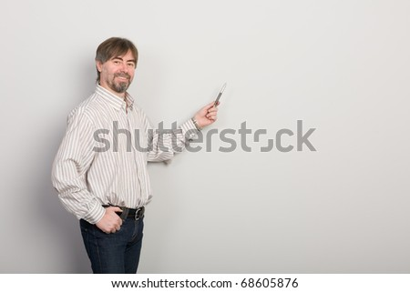 Businessman showing something on a gray background.