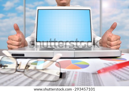 businessman showing thumb up and blank laptop on table
