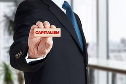 Businessman shows a wooden block with the word capitalism. Global corporate capitalism concept.