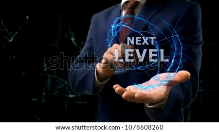 Businessman shows concept hologram Next level on his hand. Man in business suit with future technology screen and modern cosmic background