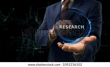 Businessman shows concept hologram Research on his hand. Man in business suit with future technology screen and modern cosmic background