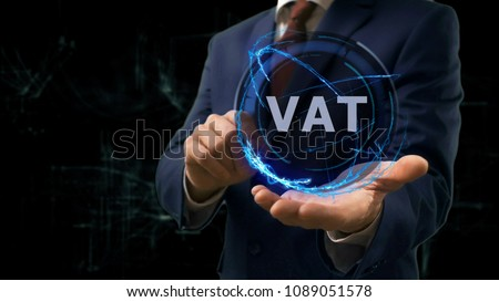 Businessman shows concept hologram VAT on his hand. Man in business suit with future technology screen and modern cosmic background