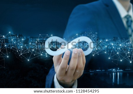 Businessman shows sign of infinity on the background of the city. The concept of unlimited Internet. #1128454295