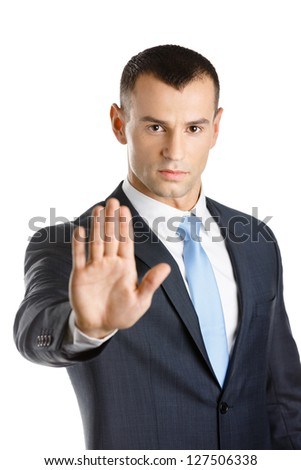 Businessman shows stop gesture, isolated on white