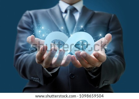 Businessman shows the infinity symbol on a blue background. #1098659504