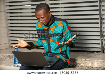 Businessman shrugging and gesturing indifference as he read the screen of his handheld in astonishment. #1503515336