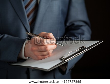Businessman signing a contract, black background