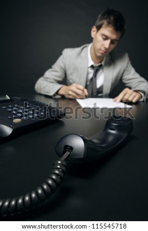 businessman signing a document, focus on telephone handset