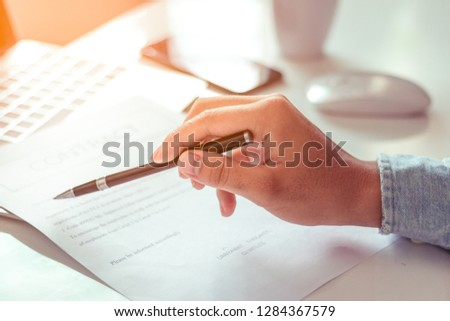 Businessman signing a document in office #1284367579