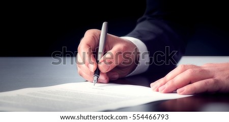 Businessman Signing An Official Document #554466793