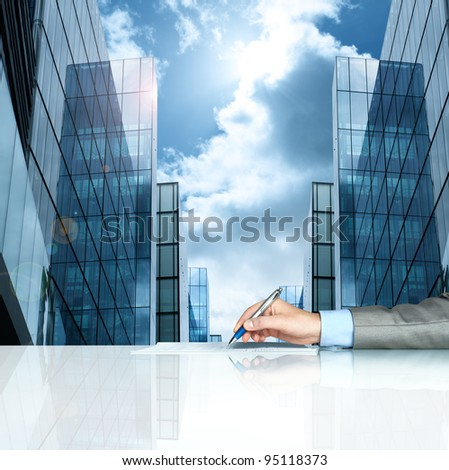 Businessman signing contract against modern offices