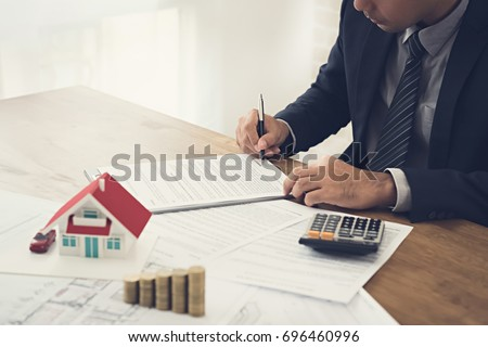 Businessman signing contract agreement with document, money and house model on the table - real estate, properties and investment concepts