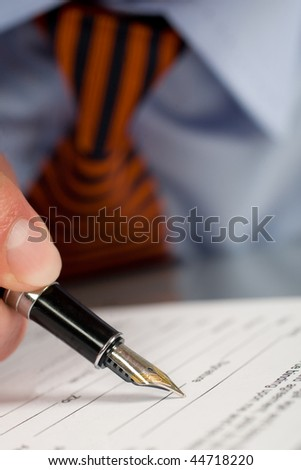 Businessman signing contract with pen