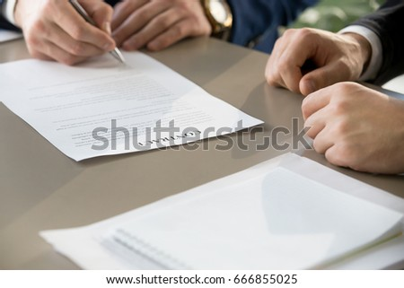 Businessman signing financial contract at formal meeting, male hand putting signature after reaching agreement and making deal, business partnership concept, focus on legal document, close up view