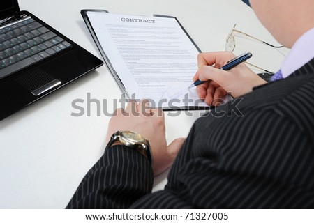 Businessman signs a contract at the table in the office