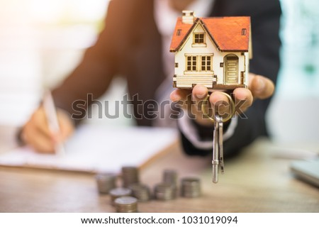 Businessman signs contract behind home architectural model Foto stock ©