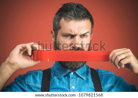 Businessman silenced with duct tape over his mouth. Bearded man with wrapping adhesive tape around mouth. Unhappy man in denim shirt covered mouth with red insulating tape. Isolated on red background. #1079821568