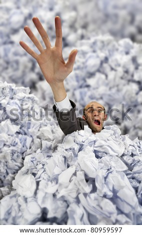 Businessman sinking in big heap of crumpled papers and asking for help