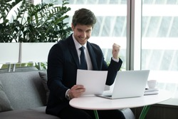 Businessman sit at desk read paper financial documents feels excited by sales increase, celebrate profitable deal, receive lucrative contract, good project results, entrepreneur get bank loan approval