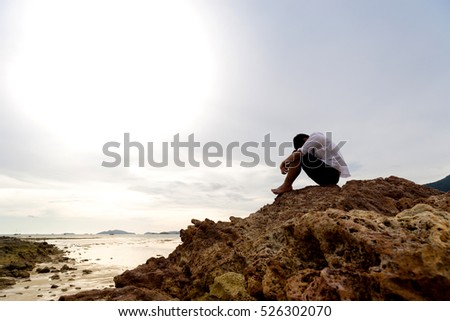 Shutterstock Businessman sit on the rocks but he is scared and alone