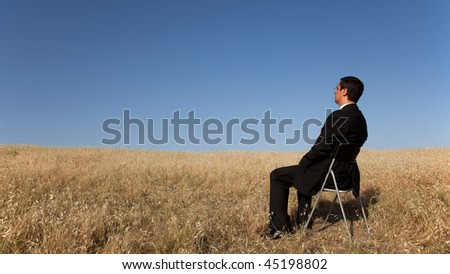businessman sited in a chair looking to the landscape