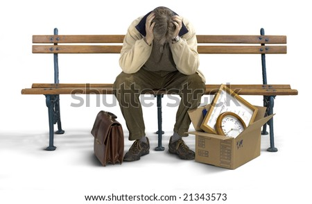 Businessman siting on a bench looking depressed with his stuff packed in a box.