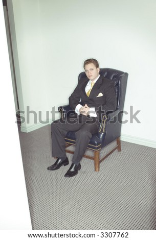 Businessman sits in his business chair looking up at the camera in his black suit and gold tie