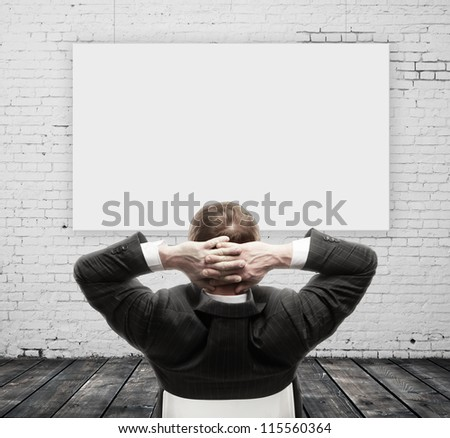 businessman sitting and empty poster - stock photo