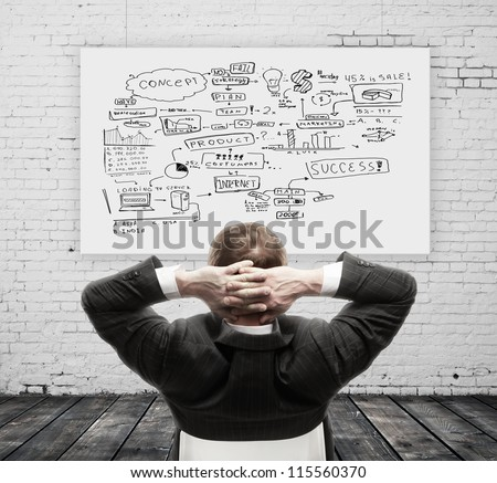 businessman sitting and scheme on wall