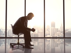 businessman sitting and thinking near office window