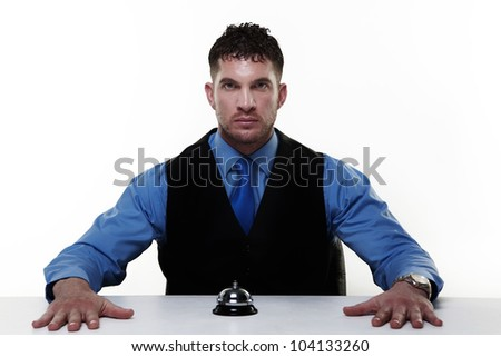businessman sitting at a desk with a call bell infront of him