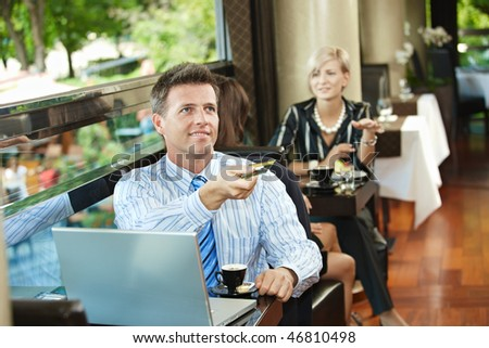 Businessman sitting at coffe table in cafe, paying with credit card, smiling.